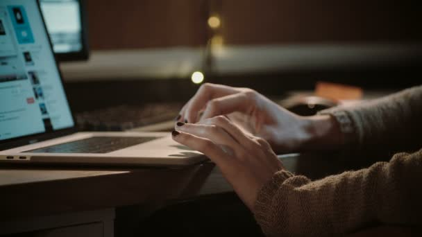 Girl hands on a laptop touchpad. Close-up. Woman in sweater surfing the web in the dark at home. Entertainment. 4K.