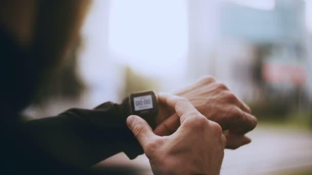 4 k běžec počáteční smartwatch časovač a běh. Muž nastavení časovače tracker smartwatch před jogging. Detailní záběr pov.