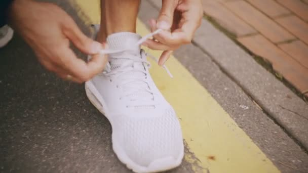 4 k detail vázání tkaničky na Bílé tenisky. Sportovec s kroužkem šněrování bílé sportovní boty na asfaltové trati město
