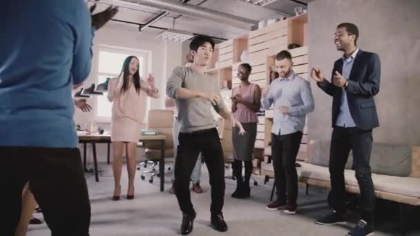 Happy Japanese employee doing funny dance moves at casual office celebration party. Team celebrates success slow motion.