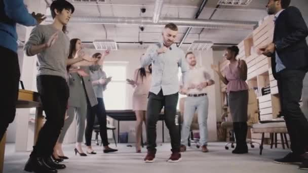 Excited multiethnic business people dance in circle at office teambuilding party, celebrating achievements slow motion.