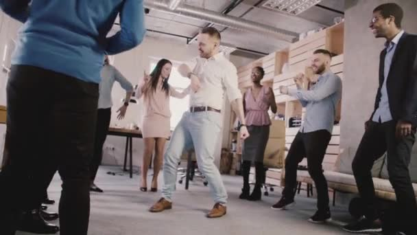 Happy European businessman dancing with colleagues in circle at teambuilding corporate celebration party slow motion.