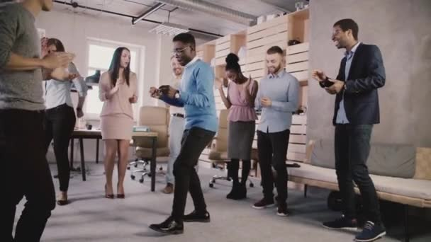 Happy African American boss dancing with employees at office teambuilding party, celebrating team success slow motion.