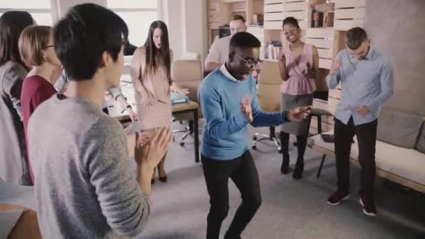 Cheerful African American manager dancing in circle with colleagues at fun casual office celebration party slow motion.
