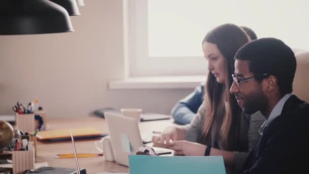 Happy multiethnic millennial business people work together by the table in modern light loft healthy office, slow motion