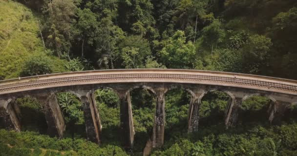 Drone static top view of people standing on Nine Arch Bridge Ella in Sri Lanka, ancient tourism destination landmark.