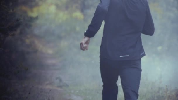 Slow motion. Man running away into foggy forest. Escaping trouble. Exploring mysterious deep woods. Lonely runaway.