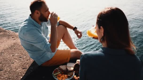 Young happy couple sitting near water and eating lunch. Romantic date of beautiful man and woman on the shore of sea.