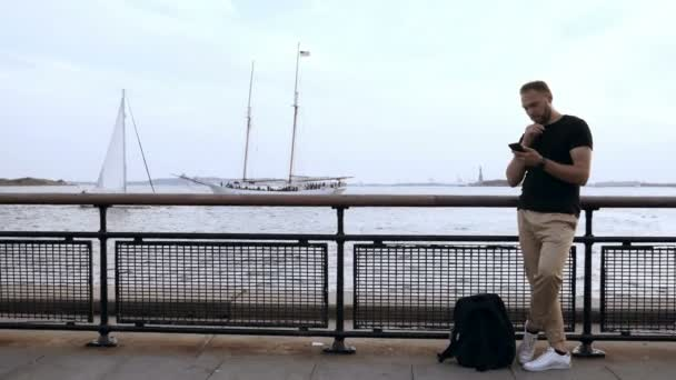 Young handsome man standing on the pier near the fence and using smartphone near the water, browsing the Internet.