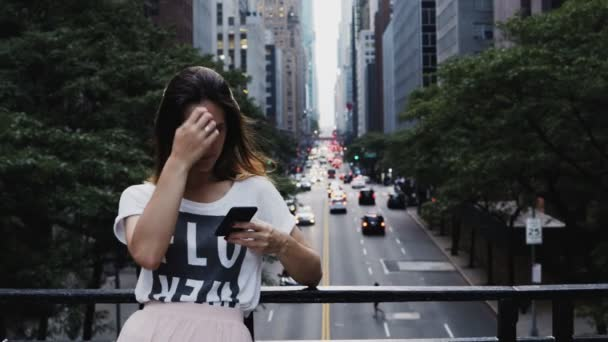 Young beautiful woman standing on the bridge near the traffic road and using the smartphone in New York, America.