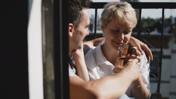 Young happy romantic couple having coffee at lovely apartment balcony with bronze metallic mugs, hug, talk and smile.