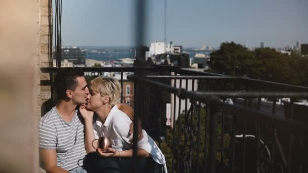 Happy relaxed multiethnic romantic couple sitting close together at a lovely sunny morning balcony in New York.