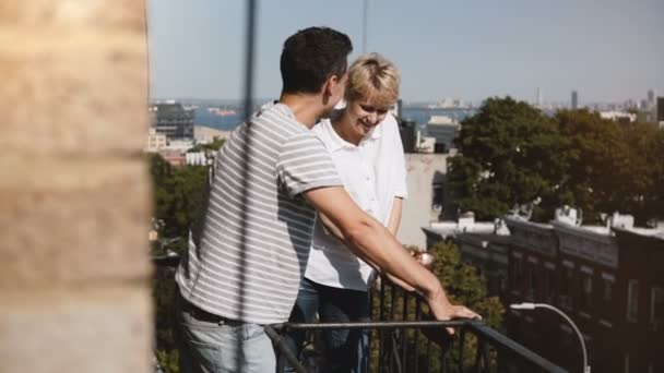 Beautiful young romantic couple standing together, enjoying talking at a small sunny balcony with lovely New York view.