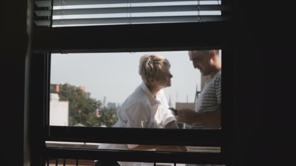 Happy smiling romantic couple standing at a small sunny balcony, view through apartment window, using smartphones.
