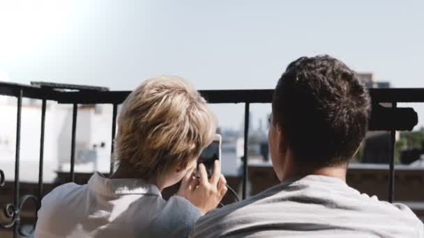 Happy romantic couple sitting at a small sunny balcony, taking smartphone photos of amazing Manhattan view in New York.