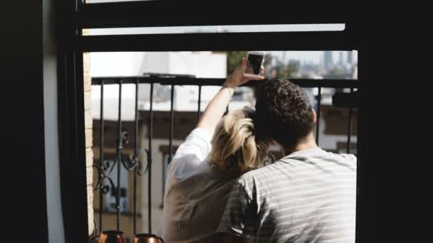 Back view happy young couple sitting at a small sunny summer New York apartment balcony, taking smartphone selfie.