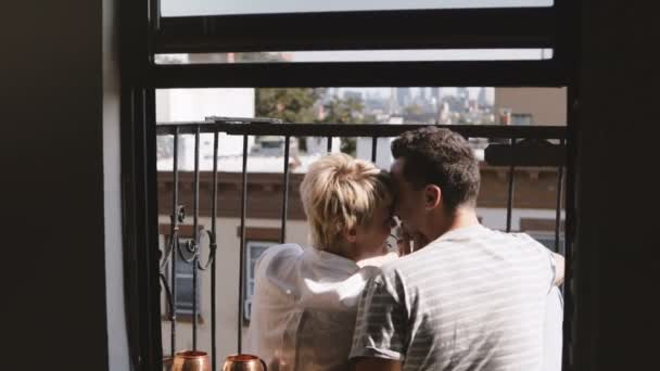 Back view happy romantic couple sitting at a small New York apartment balcony, kissing and taking smartphone selfie.