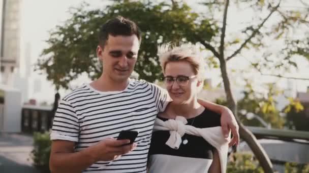 Zpomalený pohyb spokojený úsměv mladý muž hispánského původu a Evropská žena chůze objímání, pomocí smartphone za jasného letního dne.