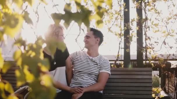 Slow motion klidný romantický pár sedí blízko sebe na podzimní lavičce v parku a mluví o plány a sny.