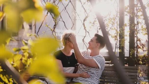 Zpomaleně se uvolnil, usmívající se mladý muž a žena mluvila na podzimní lavička těší Krásný slunečný den.