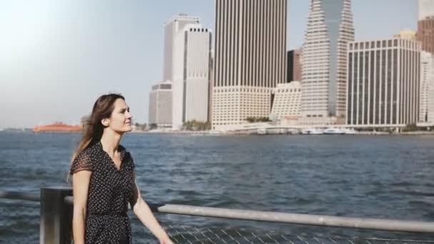 Amazing panning shot of happy European woman with flying hair walking along famous Manhattan Island riverside skyline.