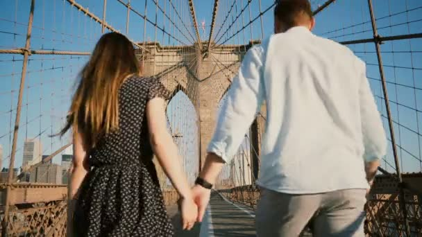 Romantic couple walk along Brooklyn Bridge NYC, hold hands and kiss on a beautiful summer day, back view low angle 4K. Adult man and woman share lovely bonding time together in amazing urban cityscape