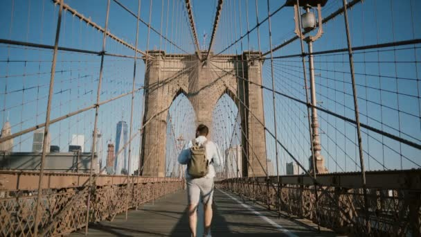Happy male tourist walking away from camera back view, looking around along Brooklyn Bridge, New York on a sunny day 4K.