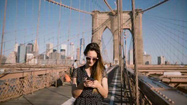 Beautiful Caucasian businesswoman in stylish sunglasses stands using smartphone messenger app at Brooklyn Bridge 4K.
