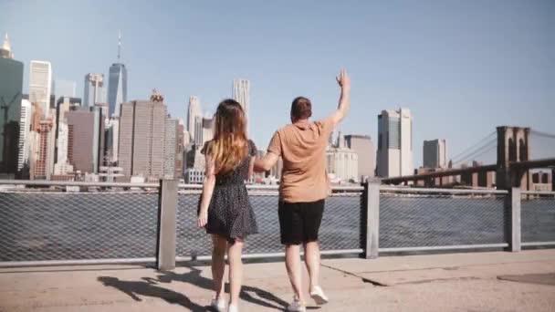 Happy European tourist couple run up holding hands arms raised to amazing Manhattan skyline, Brooklyn Bridge slow motion
