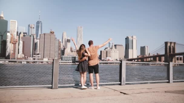 Happy Caucasian couple stand hugging, arms raised at amazing Manhattan skyline in New York, walk unimpressed slow motion