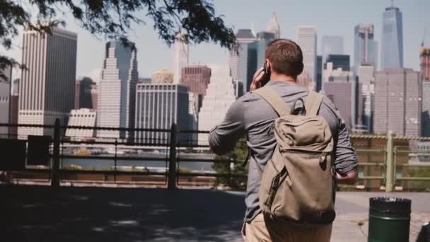 Camera follows happy successful businessman walking, talking on the phone at Manhattan skyline, New York, slow motion.