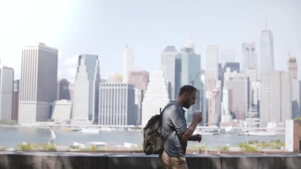 Happy successful European freelance worker walking along epic Manhattan skyline in New York with coffee and smartphone.