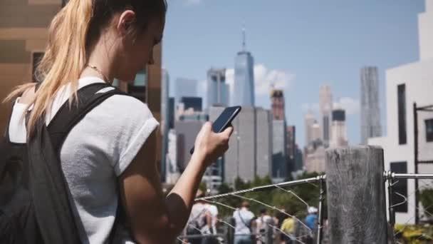 Beautiful Caucasian girl confused looking at smartphone near amazing Manhattan financial center panorama, New York City.