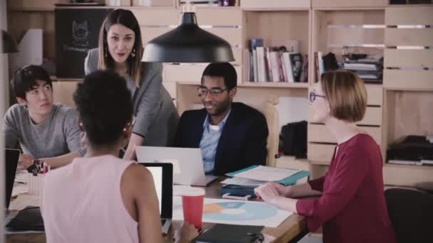 Positive female business coach gives directions to multiethnic team. Young woman boss leads office meeting slow motion. Confident happy businesswoman motivates employees in modern healthy workplace.