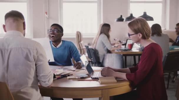 Happy smíšený etnické tým nezávislých podnikatelů spolupracovat tabulkou v moderní loft coworking úřadu