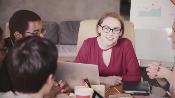 Successful beautiful European businesswoman in glasses leading a multiethnic team meeting by the table in modern office.