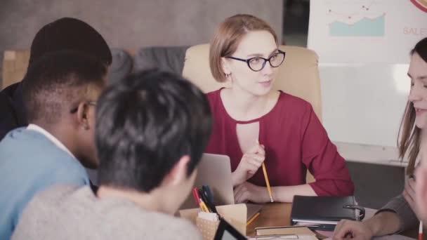 Úspěšné krásné ženské Ceo podnikatelka mluví zaměstnancům v mnohonárodnostní tým setkání v kanceláři moderní loft