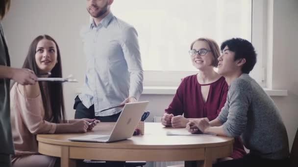 Mladí mnohonárodnostní obchodních, lidé poslouchat k nepoznání ženské vůdce, pokračovat v diskusi v moderní zdravé kanceláře