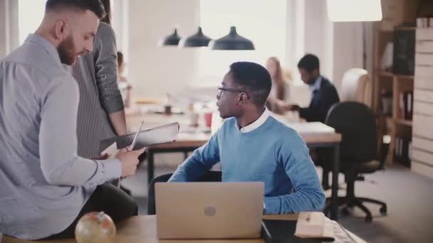 Dva mladí mnohonárodnostní kolegové spolupracovat v moderní loft Coworkingové, vytížené kanceláři týmovou práci na pozadí