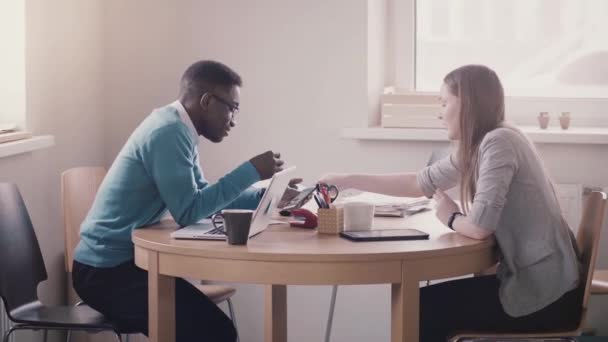 African American young office worker collaborating with European female colleague by the table looking at smartphone.