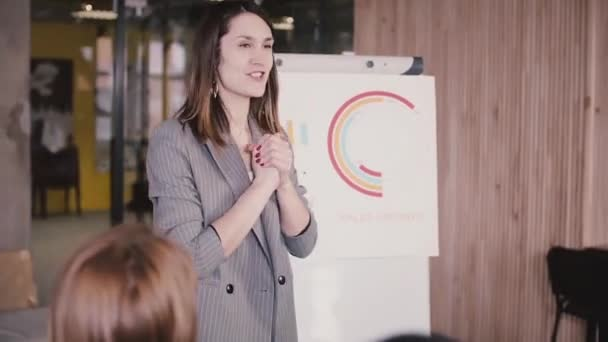 Medium shot of successful cheerful female business coach speaking to inspire office workers at marketing company team meeting. Attractive Caucasian businesswoman encouraging and motivating colleagues.