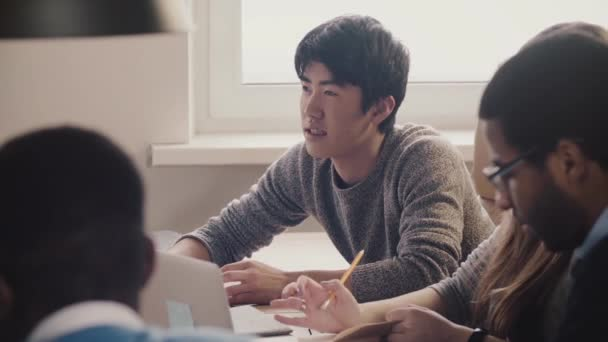 Close-up happy confident Japanese young professional businessman listening and smiling at multiethnic office meeting.