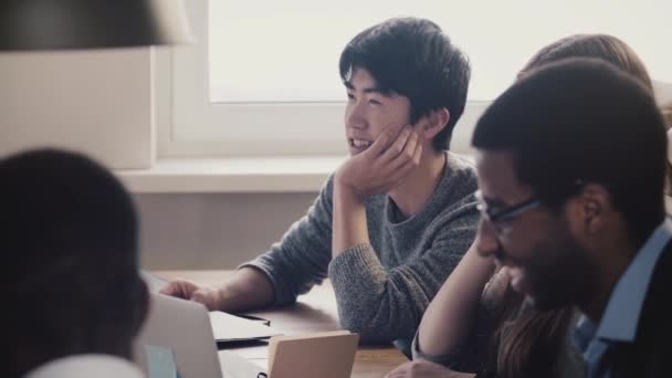 Close-up happy Japanese young employee listening and laughing together with colleagues at multiethnic office meeting.