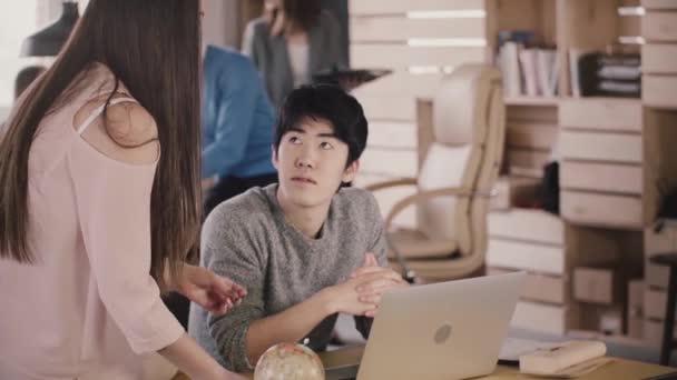 Boldog női vezetője segít fiatal japán kolléga, hogy megvitassák a munka folyamat a modern, trendi tetőtéri office lassú mozgás.