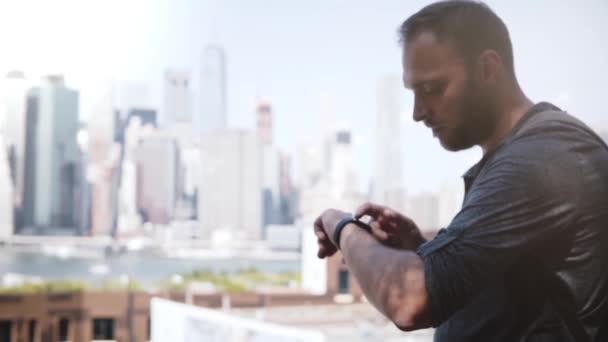 Successful European businessman smiling, using smart watch to communicate at epic Manhattan skyline, New York City.