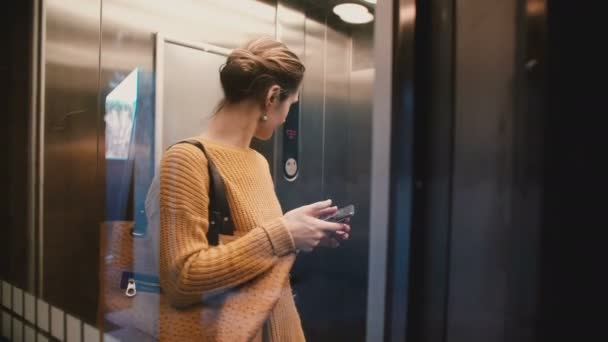 A view of attractive stressed busy Caucasian woman riding up in transparent elevator using smartphone mobile office app.