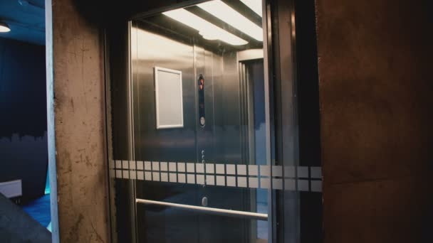 Young happy man enters elevator, pushes the button, door closes and he rides up using smartphone mobile office app.