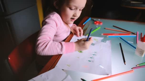 Nagy látószögű kamera csúszó jobb mint kis kaukázusi lány gyermek rózsaszín pulóver asztalnál színes ceruza rajz.