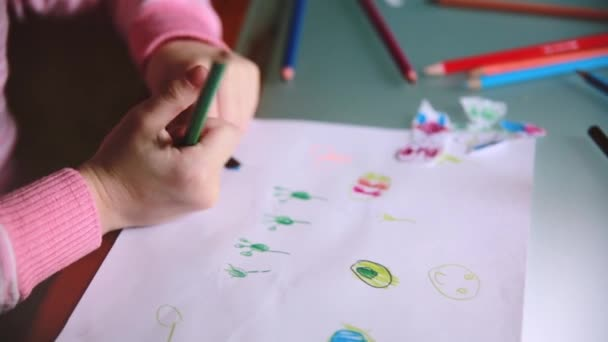 Camera sliding left over little Caucasian preschool girl hands drawing animals with colorful pencils at a table close-up