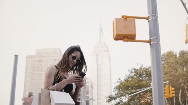 Happy beautiful Caucasian businesswoman with shopping bags in sunglasses using smartphone app near Empire State Building